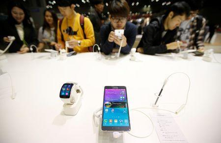 Visitors try out a Samsung Electronics' Galaxy Note 4 during the 2014 Korea Electronics Show in Goyang October 17, 2014. Samsung Electronics Co Ltd said third-quarter profit fell 60.1 percent from a year earlier to the lowest in more than three years, as earnings for the mobile division continued to shrink. Picture taken October 17, 2014. REUTERS/Kim Hong-Ji (SOUTH KOREA - Tags: BUSINESS TELECOMS SCIENCE TECHNOLOGY)