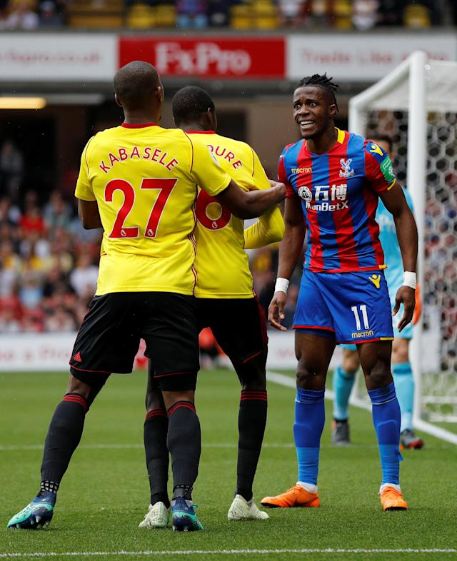 """Soccer Football - Premier League - Watford v Crystal Palace - Vicarage Road, Watford, Britain - April 21, 2018 Crystal Palace's Wilfried Zaha clashes with Watford's Abdoulaye Doucoure as Christian Kabasele intervenes REUTERS/Darren Staples EDITORIAL USE ONLY. No use with unauthorized audio, video, data, fixture lists, club/league logos or """"live"""" services. Online in-match use limited to 75 images, no video emulation. No use in betting, games or single club/league/player publications. Please contact your account representative for further details."""