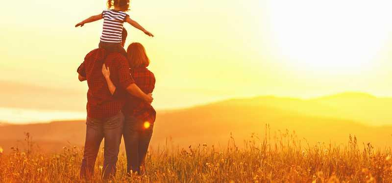 A family standing in a pasture looking at the horizon.