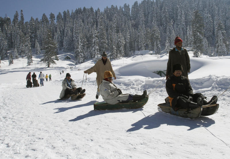 FILE- In this Feb. 7, 2013 file photo, Kashmiri laborers pull tourists on sleds in Gulmarg, some 55 kilometers (34 miles) from Srinagar, India. Kashmir's pristine Alpine landscape, ski resorts, lake houseboat stays and uninterrupted acres of apple orchards have long made it a global tourist draw. (AP Photo/Mukhtar Khan, File)