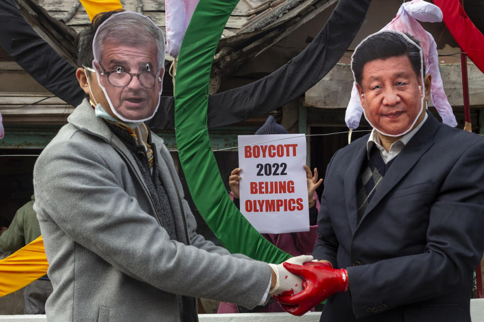 FILE - In this Feb. 3, 2021, file photo, activists wearing masks of the IOC President Thomas Bach and Chinese President Xi Jinping pose in front of the Olympic Rings during a street protest against the holding of the 2022 Winter Olympics in Beijing, in Dharmsala, India. The IOC has declined several recent requests to move the Olympics out of Beijing. (AP Photo/Ashwini Bhatia, File)