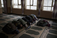 Taliban members lay their weapons down as they pray inside a mosque in Kabul, Afghanistan, Sunday, Sept. 12, 2021. (AP Photo/Felipe Dana)