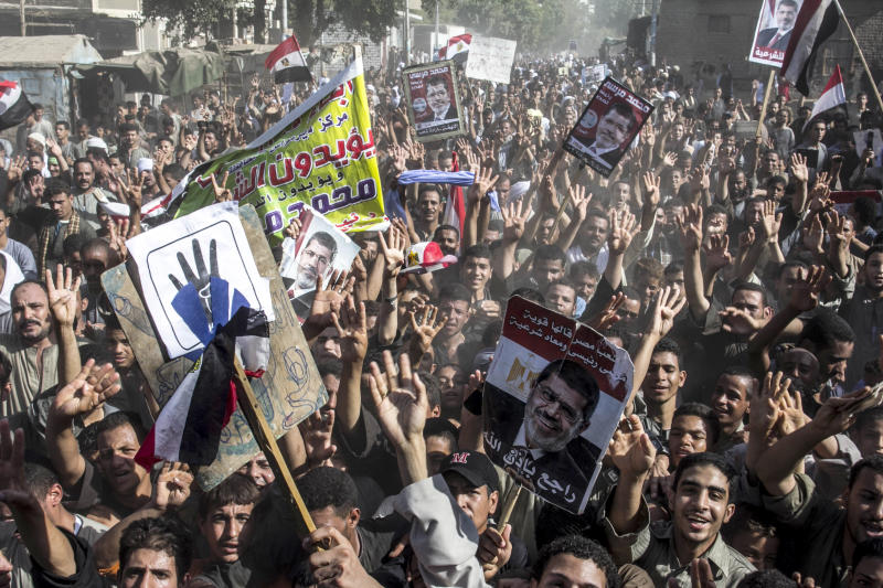 """Supporters of Egypt's ousted President Mohammed Morsi chant slogans during a demonstration in Dalga Village, in upper Egypt, Friday, Aug. 30, 2013. Tens of thousands of protesters and Muslim Brotherhood supporters rallied Friday throughout Egypt against a military coup and a bloody security crackdown, though tanks and armored police vehicles barred them from converging in major squares. The sign in the foreground reads, """"The Egyptian people said it strong - Morsi is my president and has legitimacy -- he is coming back soon.""""(AP Photo/Roger Anis, El Shorouk Newspaper) EGYPT OUT"""