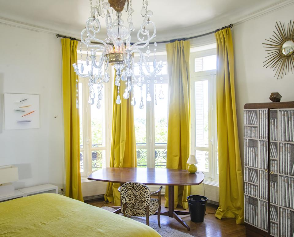 """<div class=""""caption""""> On the ceiling hangs a Spanish chandelier from the 18th century. The table is by Italian architect and designer Franco Albini for Poggi, circa 1950. The cupboard is from the 1930s covered with Fornasetti wallpaper, and on the wall is an artwork by British artist Marc Cavell. A 1930s chair is covered in velvet, and the sun mirror is from the Paris flea market. </div>"""