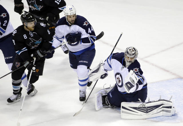 Winnipeg Jets goalie Ondrej Pavelec, right, of the Czech Republic, stops a shot next to teammate Zach Bogosian (44) and San Jose Sharks' Joe Pavelski (8) during the first period of an NHL hockey game Thursday, Jan. 23, 2014, in San Jose, Calif. (AP Photo/Marcio Jose Sanchez)