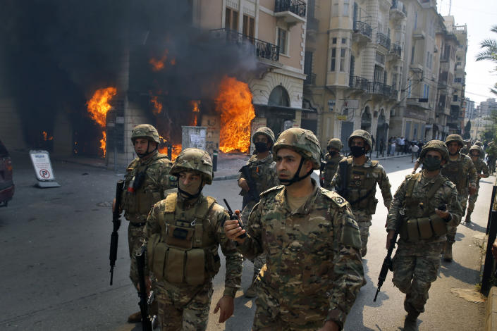 Lebanese army soldiers gather near a branch of the Credit Libanais Bank that was set on fire by anti-government protesters, in the northern city of Tripoli, Lebanon, Tuesday, April 28, 2020. Hundreds of angry Lebanese took part Tuesday in the funeral of a young man killed in riots overnight in Tripoli that were triggered by the crash of Lebanon's national currency that sent food prices soaring. (AP Photo/Bilal Hussein)