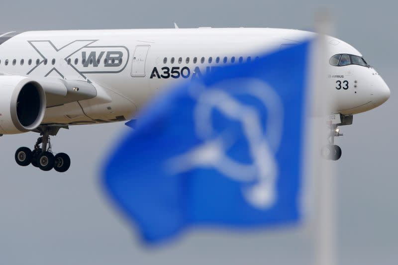 FILE PHOTO: An Airbus A350 flies over a Boeing flag while landing after a flying display during the 51st Paris Air Show at Le Bourget airport near Paris