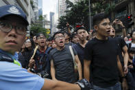 Protesters shout next to a policeman as they continue to protest an extradition bill, Sunday, June 16, 2019, in Hong Kong. Hong Kong residents Sunday continued their massive protest over an unpopular extradition bill that has highlighted the territory's apprehension about relations with mainland China, a week after the crisis brought as many as 1 million into the streets. (AP Photo/Kin Cheung)