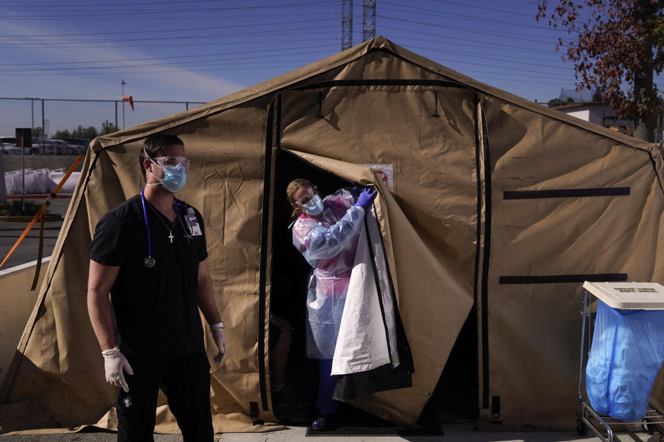Registered nurse Keith Robinson, right, watches as fellow nurse Angela Coomds calls out a patient's name from a COVID-19 triage tent at Providence Holy Cross Medical Center in the Mission Hills section of Los Angeles, Tuesday, Dec. 22, 2020. (AP Photo/Jae C. Hong)
