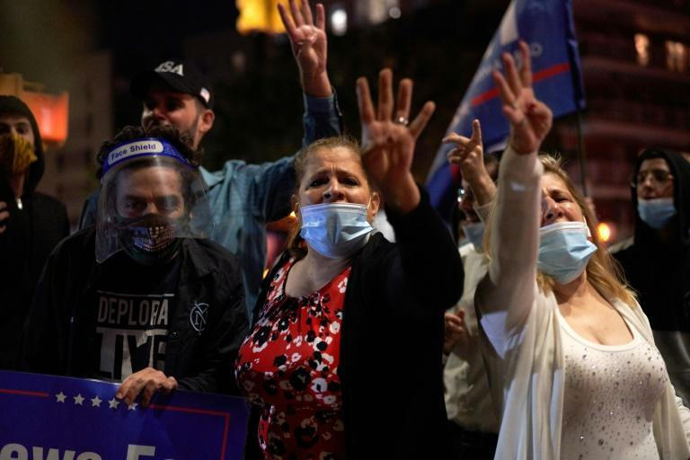 People hold Trump 2020 signs and flags as members of the Sephardic Jewish Community in Brooklyn, New York protest the closing of businesses and a new lockdown in their neighborhood on October 8, 2020