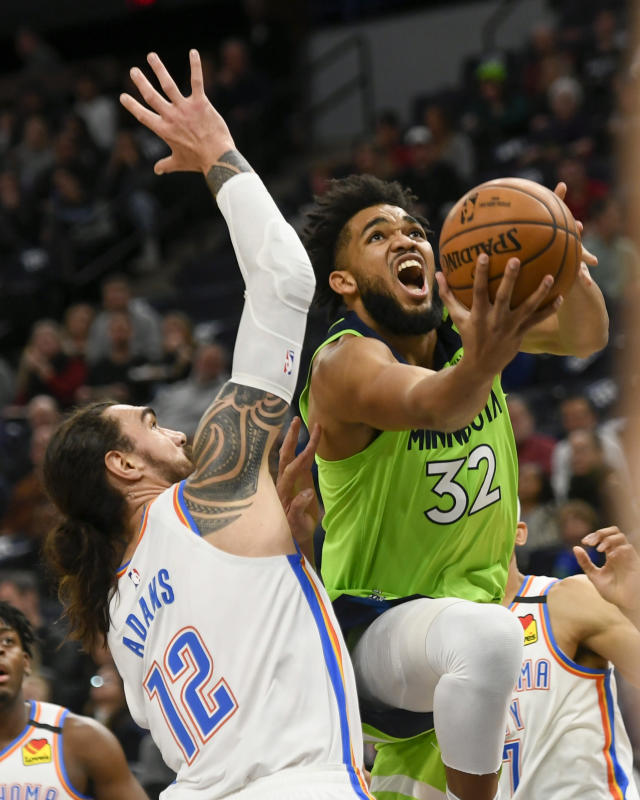 Minnesota Timberwolves center Karl-Anthony Towns(32) goes up to shoot past Oklahoma City Thunder center Steven Adams(12) during the first half of an NBA basketball game Saturday, Jan. 25, 2020, in Minneapolis. (AP Photo/Craig Lassig)