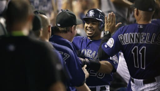 Colorado Rockies' Wilin Rosario is congratulated by teammates and coaches after he hit a solo home run against Milwaukee Brewers during the fifth inning of a baseball game in Denver on Tuesday, Aug. 14, 2012. (AP Photo/Joe Mahoney)