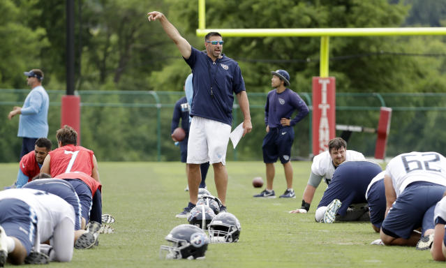 In this June 13, 2018 photo, Tennessee Titans head coach Mike Vrabel, center, watches as players warm up during NFL football minicamp in Nashville, Tenn. The Titans wrap up their first offseason under their new coach with the end of a three-day minicamp. Now they're off until the end of July and training camp. (AP Photo/Mark Humphrey)
