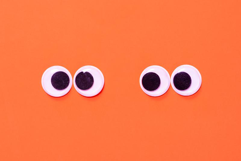 Googly eyes: One pair strabismus and squint mad googly eyes and one pair normal funny eyes next to each other on orange background.