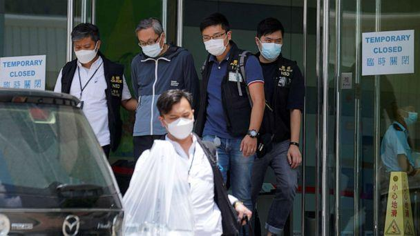PHOTO: Police officers from the national security department escort Apple Daily's Chief Executive Officer Cheung Kim-hung from the offices of Apple Daily and Next Media in Hong Kong, China, June 17, 2021. (Lam Yik/Reuters)