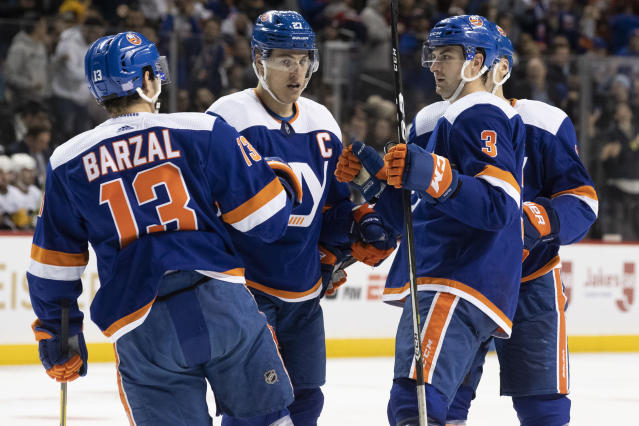 New York Islanders defenseman Adam Pelech (3) celebrates his goal against the Pittsburgh Penguins with centers Mathew Barzal (13) and Anders Lee (27) during the second period of an NHL hockey game, Thursday, Nov. 7, 2019, in New York. (AP Photo/Mary Altaffer)