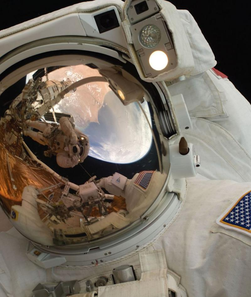 A close-up of Astronaut John Grunsfeld shows the reflection of Astronaut Andrew Feustel, perched on the robotic arm and taking the photo. The pair teamed together on three of the five spacewalks during Servicing Mission 4 in May 2009.