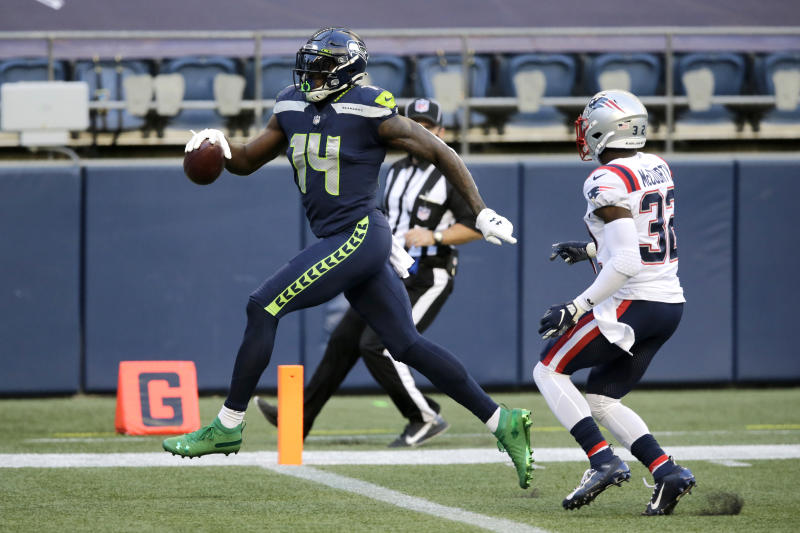 Seattle Seahawks wide receiver DK Metcalf, left, scores a touchdown ahead of New England Patriots free safety Devin McCourty, right, during the first half of an NFL football game, Sunday, Sept. 20, 2020, in Seattle. (AP Photo/John Froschauer)