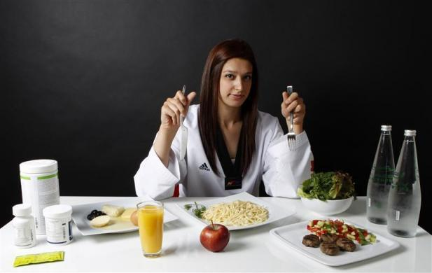 Turkish Taekwondo fighter and Olympic hopeful Nur Tatar, 20, poses in front of her daily food intake in Ankara May 24, 2012. Tatar is preparing to compete for Turkey in the London 2012 Olympic Games. This is her first time competing in the Olympics and she is on a strict diet to shed several pounds to reach the exact weight category in which she will fight. She has reduced her daily calorie intake to 1500 kcal.