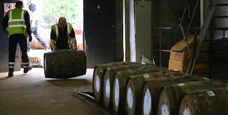 In this photo taken June 30, 2016, a worker rolls in a barrel of whisky at The Macallan distillery in Craigellachie, Scotland. The distillery, famous for its single-malt whisky offers a detailed tour explaining what goes into making the product. (Michelle Locke via AP)