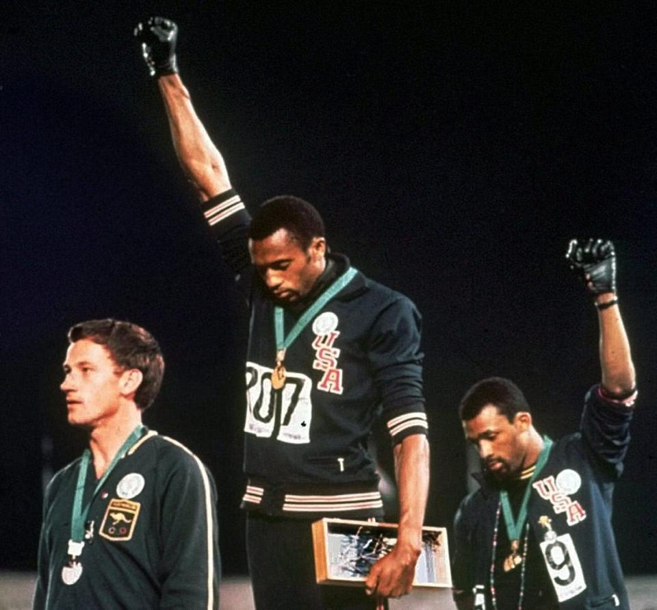 Australian silver medalist Peter Norman stands on the medal podium as Americans Tommie Smith and John Carlos raise their gloved fists in a human rights protest.