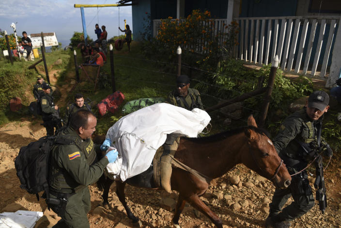 Police officers transport the body of one of at least five people killed during a skirmish between illegal armed groups in Jamundi, southwest Colombia, Friday, Jan. 17, 2020. Authorities say rebels with the former Revolutionary Armed Forces of Colombia operate in the area and may have been involved. (AP Photo/Christian EscobarMora)