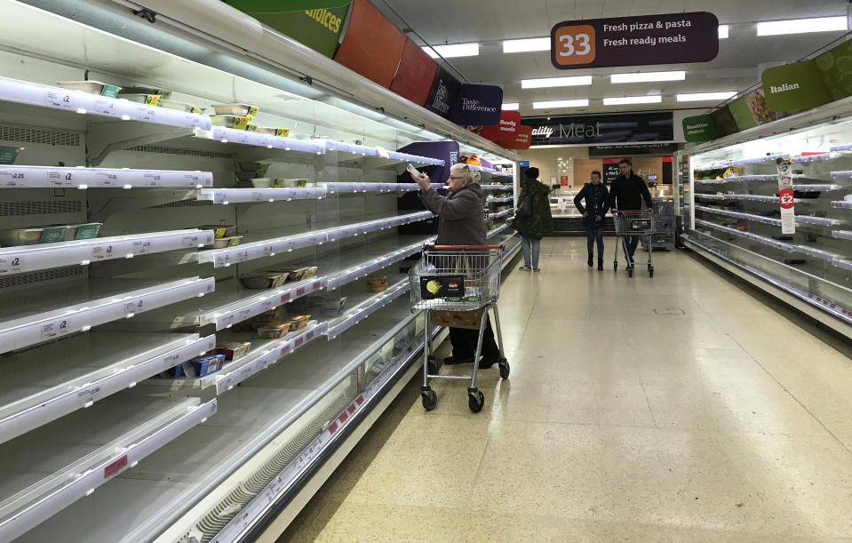 An elderly woman reaches up to a near empty shelf in a supermarket in London, Thursday, March 19, 2020. For most people, the new coronavirus causes only mild or moderate symptoms, such as fever and cough. For some, especially older adults and people with existing health problems, it can cause more severe illness, including pneumonia.(AP Photo/Kirsty Wigglesworth)