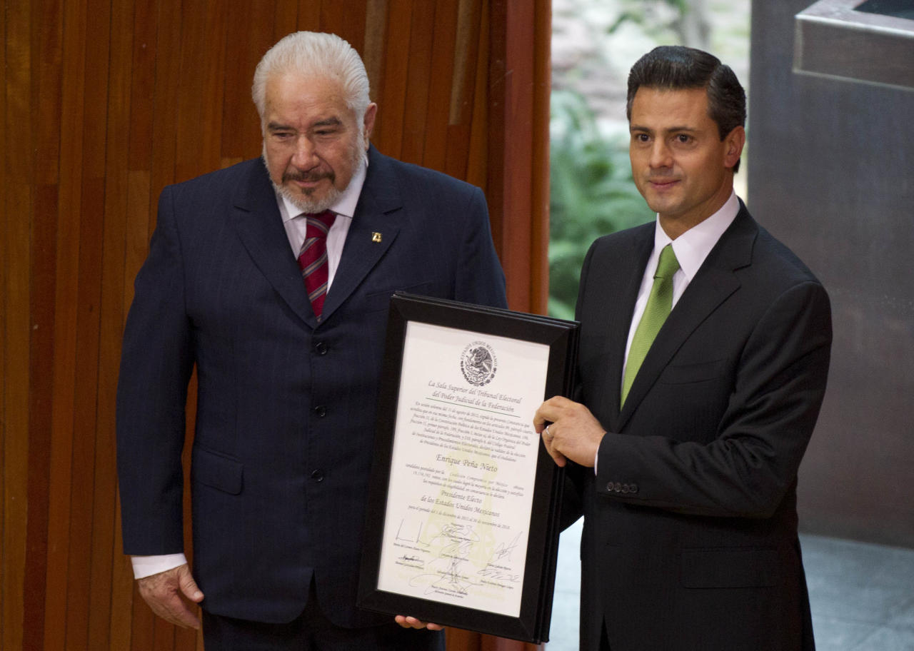 Mexico's President-elect Enrique Pena Nieto, right, of the former ruling Institutional Revolutionary Party (PRI), right, alongside Jose Luna Ramos, president of the magistrates of Mexico's Federal Electoral Tribunal (TRIFE), holds up a document issued by the TRIFE that declares he won the majority of votes in last July's presidential election in Mexico City, Friday, Aug. 31, 2012. Pena Nieto will be sworn-in to office on Dec. 1. (AP Photo/Eduardo Verdugo)