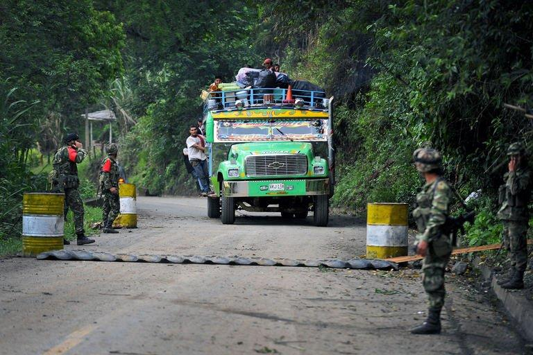 "A ""chiva"" (public transportation) passes a checkpoint in El Palo, department of Cauca, Colombia, on February 5, 2013, after car bombs planted by FARC exploded"
