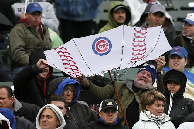 A fan has his umbrella flipped inside out by the wind during the fifth inning of a baseball game between the Chicago Cubs and the Milwaukee Brewers on Friday, May 16, 2014, in Chicago. (AP Photo/Andrew A. Nelles)