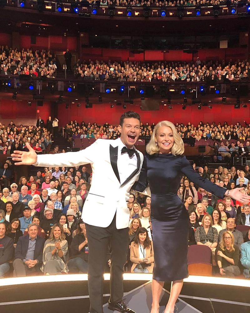 Kelly Ripa and Ryan Seacrest pose on stage