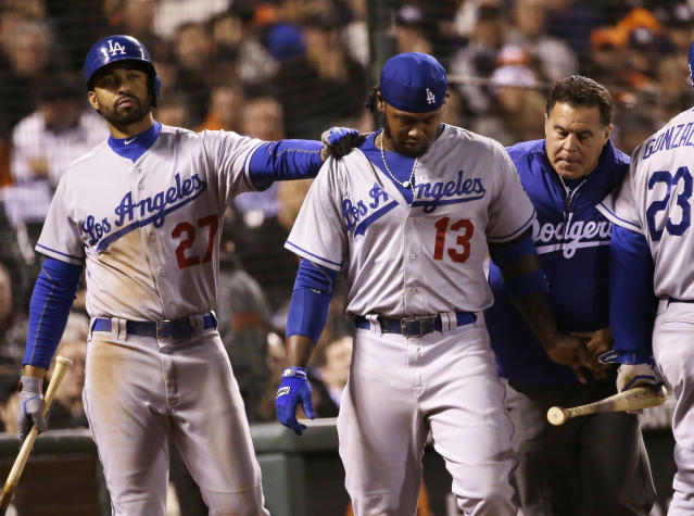 Los Angeles Dodgers' Hanley Ramirez, center, walks off the field as teammate Matt Kemp (27) gives him a pat on the shoulder after Ramirez was hit by a throw from San Francisco Giants' Ryan Vogelsong during the seventh inning of a baseball game on Wednesday, April 16, 2014, in San Francisco. (AP Photo/Marcio Jose Sanchez)