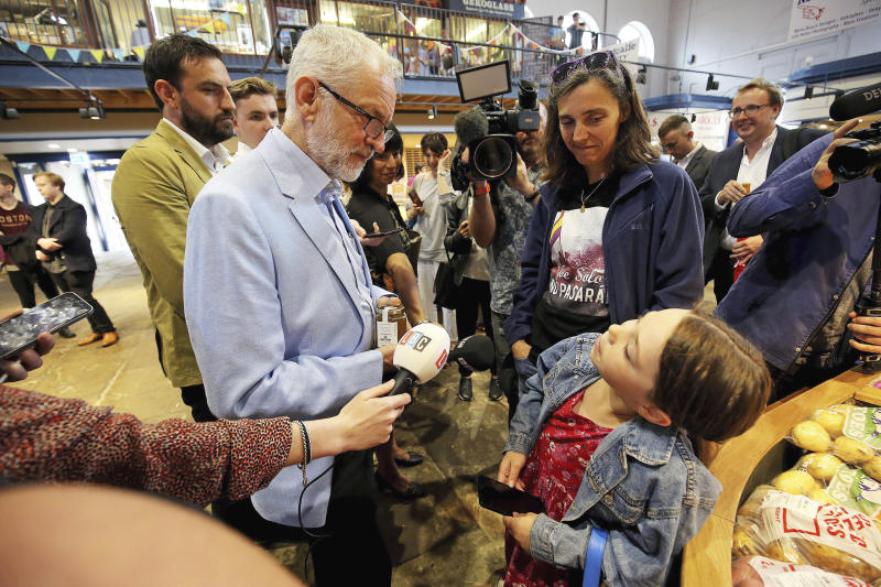 Britain's Labour leader Jeremy Corbyn speaks to a young girl, during a visit to Scarborough Public Market to discuss the impact of a no-deal Brexit on food bills, in Scarborough, England, Friday, Aug. 2, 2019. (Nigel Roddis/PA via AP)