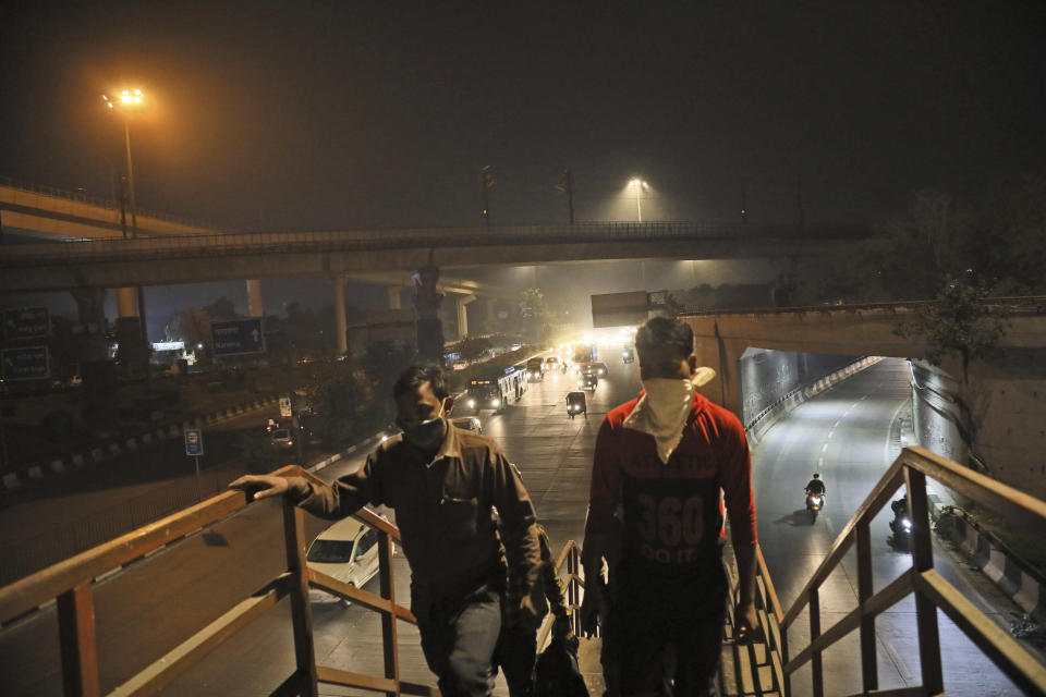 Pedestrians walk on an overbridge on a street covered with smog in New Delhi, India, Thursday, Nov. 5, 2020. A thick quilt of smog lingered over the Indian capital and its suburbs on Friday, fed by smoke from raging agricultural fires that health experts worry could worsen the city's fight against the coronavirus. Air pollution in parts of New Delhi have climbed to levels around nine times what the World Health Organization considers safe, turning grey winter skies into a putrid yellow and shrouding national monuments. (AP Photo/Manish Swarup)