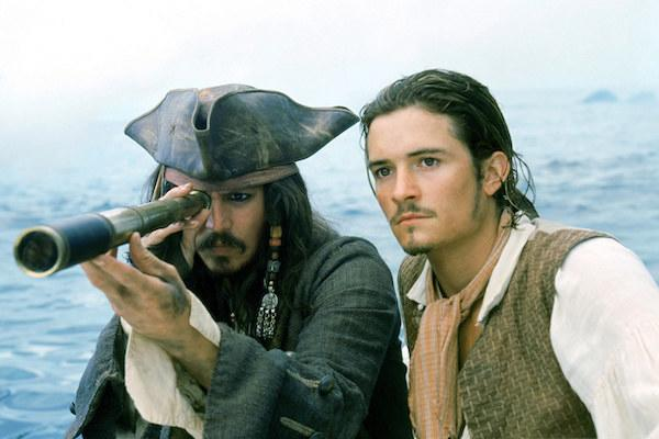 Johnny Depp looking through a spyglass while Orlando Bloom stares ahead.