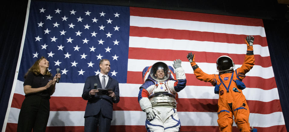 WASHINGTON, DC - OCTOBER 15: In this NASA handout, Amy Ross, a spacesuit engineer at NASAs Johnson Space Center, left, and NASA Administrator Jim Bridenstine, second from left, watch as Kristine Davis, a spacesuit engineer at NASAs Johnson Space Center, wearing a ground prototype of NASAs new Exploration Extravehicular Mobility Unit (xEMU), and Dustin Gohmert, Orion Crew Survival Systems Project Manager at NASAs Johnson Space Center, wearing the Orion Crew Survival System suit, right, wave after being introduced by the administrator, October15, 2019 at NASA Headquarters in Washington. The xEMU suit improves on the suits previous worn on the Moon during the Apollo era and those currently in use for spacewalks outside the International Space Station and will be worn by first woman and next man as they explore the Moon as part of the agencys Artemis program. The Orion suit is designed for a custom fit and incorporates safety technology and mobility features that will help protect astronauts on launch day, in emergency situations, high-risk parts of missions near the Moon, and during the high-speed return to Earth. (Photo byu Joel Kowsky/NASA via Getty Images)