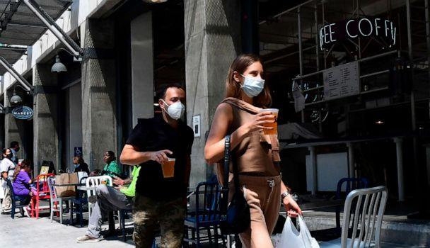 PHOTO: People wearing face masks carry their pints of beer past tables for outdoor dining in Los Angeles, California, on July 1, 2020. (Frederic J. Brown/AFP via Getty Images)