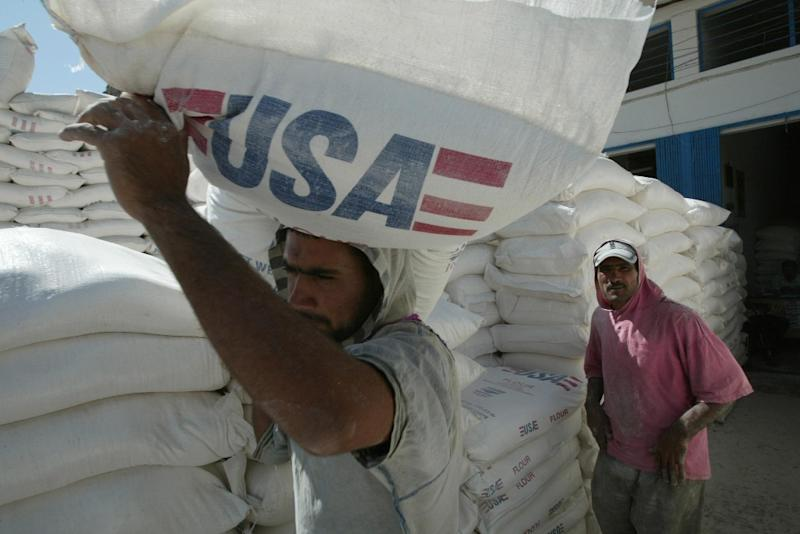 Iraqi workers haul sacks of flour donated by the United States in the Sadr City locality of Baghdad on September 11, 2003