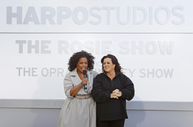 """FILE-This Sept. 15, 2011, file photo shows Rosie O'Donnell, right, and Oprah Winfrey speaking to the media after the unveiling of a new sign outside Harpo Studios welcoming """"The Rosie Show,"""" to the studio in Chicago. Winfrey is selling Harpo Studios in Chicago to a developer, but the studio will remain on the property for another two years. Harpo Inc. said in a statement that it has entered into a purchasing agreement with Sterling Bay Cos. for the four-building campus on Chicago's West Side. (AP Photo/M. Spencer Green, File)"""