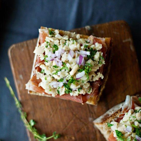 """<p>Strips of prosciutto top each toast and are topped in turn with a mound of creamy white beans and sprinkling of crisp red onion.</p><p><a href=""""https://www.foodandwine.com/recipes/white-bean-and-prosciutto-bruschetta"""">GO TO RECIPE</a></p>"""