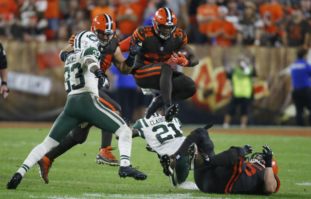 Cleveland Browns running back Carlos Hyde (34) jumps over defenders during the second half of an NFL football game against the New York Jets, Thursday, Sept. 20, 2018, in Cleveland. (AP Photo/Ron Schwane)