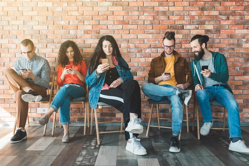 Millennials workforce mobility. Young people working in modern loft office, using smartphones. Modern technology advantages.