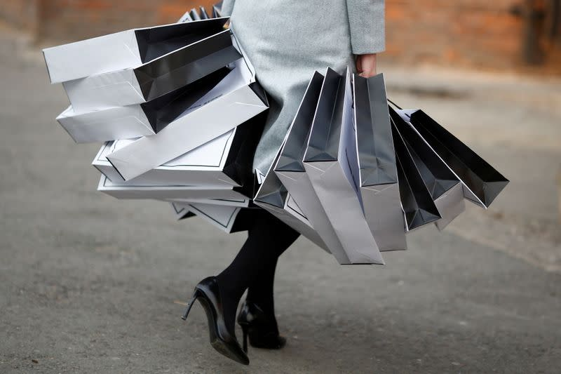 FILE PHOTO: A staff member carries bags at China Fashion Week in Beijing