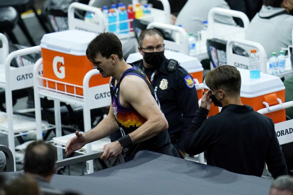 In injured Phoenix Suns forward Dario Saric is taken to the locker room during the first half of Game 1 of basketball's NBA Finals against the Milwaukee Bucks, Tuesday, July 6, 2021, in Phoenix. (AP Photo/Ross D. Franklin)