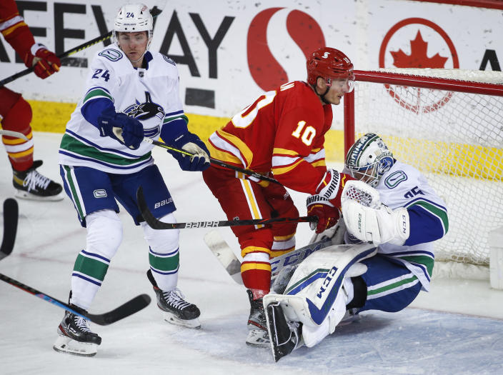 Vancouver Canucks' Jimmy Vesey, left, checks Calgary Flames' Derek Ryan, center, into goalie Thatcher Demko during the second period of an NHL hockey game Thursday, May 13, 2021, in Calgary, Alberta. (Jeff McIntosh/The Canadian Press via AP)