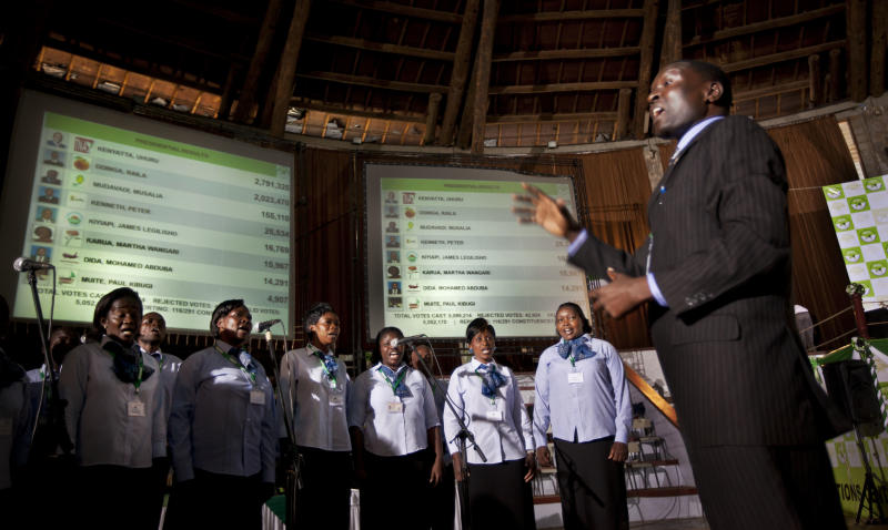 In an attempt to fill the long stretches of time without briefings to the media or announcement of electoral results, a choir sings songs in front of electoral results boards at the National Tallying Center, in Nairobi, Kenya Thursday, March 7, 2013. Kenyan media members told The Associated Press on Thursday that the Media Owners Association agreed not to sensationalize headlines or even put political press conferences live on the air, to avoid airing hate speech or political attacks that could incite violence. (AP Photo/Ben Curtis)
