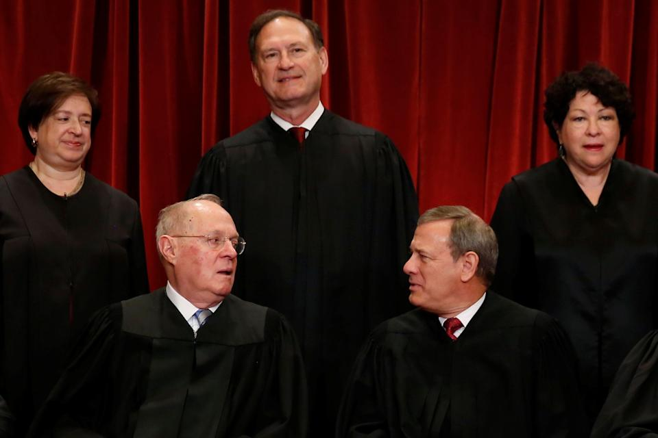 U.S. Supreme Court Justice Anthony Kennedy (bottom L) chats with Chief Justice John Roberts (bottom R) during a new U.S. Supreme Court family photo including Justice Neil Gorsuch (not pictured), their most recent addition, at the Supreme Court building in Washington, D.C., U.S., June 1, 2017. Also pictured are Justice Elena Kagan (back row, L-R), Justice Samuel Alito and Justice Sonia Sotomayor. REUTERS/Jonathan Ernst