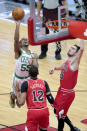 Boston Celtics' Jeff Teague (55) shoots over Daniel Gafford (12) and Tomas Satoransky during the first half of an NBA basketball game Monday, Jan. 25, 2021, in Chicago. (AP Photo/Charles Rex Arbogast)