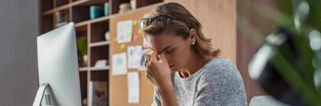 Woman looking stressed at her office desk.
