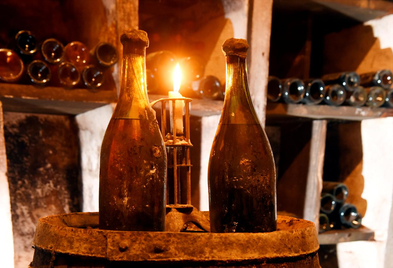 """Two bottles, of three vintage bottles of vin jaune """"yellow wine"""" from 1774, are presented in a cellar in Arbois, France, May 22, 2018 before the three bottles are put up for auction in Lons le Saunier on May 26th.  REUTERS/Jean-Pierre Amet"""